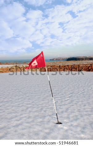 flag on a snow covered golf course in ireland in winter with sea and cliffs in background - stock photo