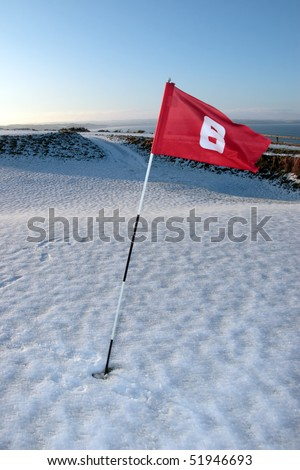 flag on a snow covered links golf course in ireland in winter - stock photo