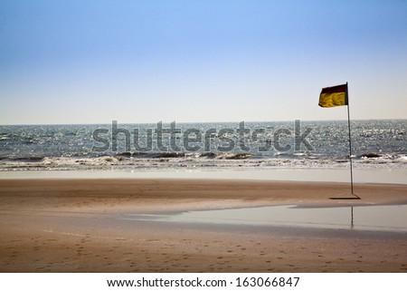 Flag on the beach, Morjim, Pernem, Goa, India - stock photo