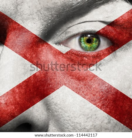 Flag painted on face with green eye to show Alabama support - stock photo