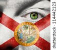 Flag painted on face with green eye to show Florida support - stock photo