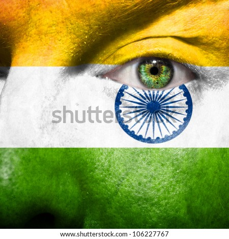 Flag painted on face with green eye to show india support - stock photo