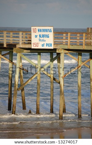 "Flagler Pier safety ""No swimming or surfing"" sign - stock photo"