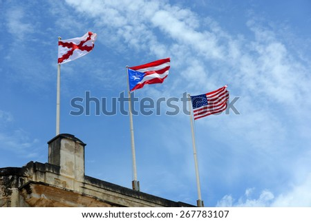 Flags fly at Castillo de San Cristóbal, San Juan, Puerto Rico. Three flags from left to right are Burgundy Cross, Puerto Rico flag and USA flag.  - stock photo