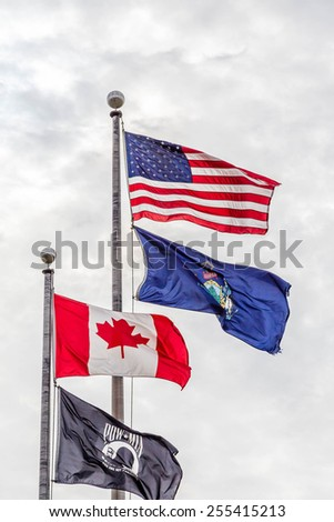 Flags of America, Canada, Maine and POW/MIA flying under cloudy skies in Portland, Maine - stock photo