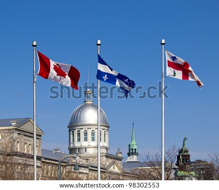 Flags of Canada, Quebec and Montreal on masts in Montreal's Old Port district - stock photo