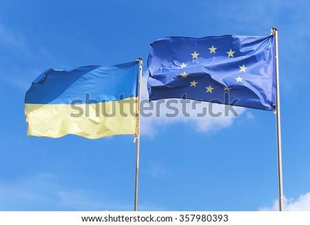 Flags of European Union and Ukraine waving on flagpoles on blue sky background - stock photo