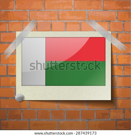Flags of Madagascar scotch taped to a red brick wall.  Rasterized version - stock photo