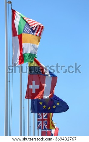 flags of many nations in the wind on a sunny day with blue sky - stock photo