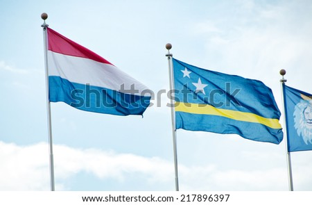 Flags of Netherlands and Curacao on Flag Poles Against Blue Sky - stock photo