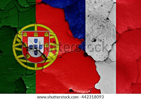 flags of Portugal and France painted on cracked wall - stock photo