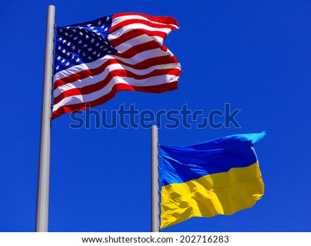 flags of the USA and Ukraine against bright blue sky - stock photo