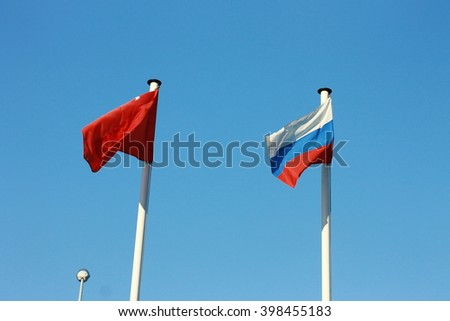 Flags of Turkey and Russia on the blue sky background - stock photo