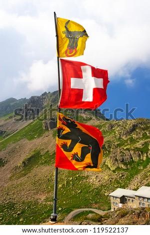 Flags of Uri Canton, Switzerland and Bern Canton on the Susten Pass. Switzerland - stock photo