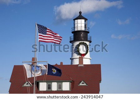 Flags wave in front of Portland Head lighthouse. - stock photo
