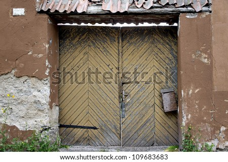 Flaking yellow grunge door with old wooden mailbox - stock photo