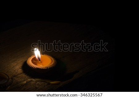 flame light on small pottery candle base. object's on wood floor in dark area. black background color. - stock photo