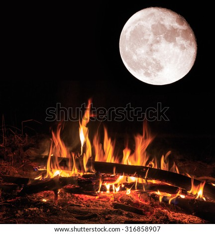 Flame of camp fire and big moon at night - stock photo