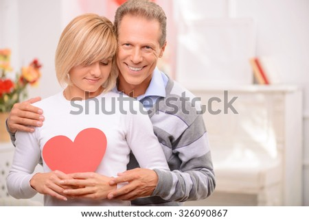 Flame of love. Pleasant happy adult couple bonding to each other end expressing warm feelings while celebrating St Valentine day - stock photo