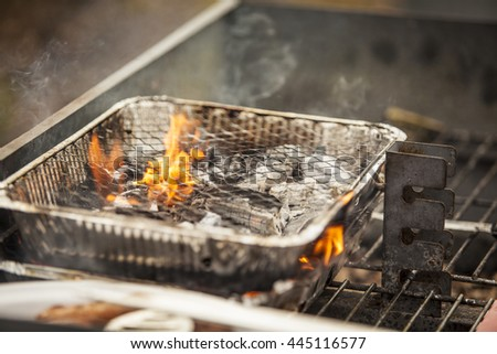 Flames coming from the coals of a small disposable barbecue - stock photo