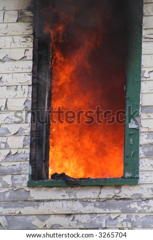 Flames engulfing the inside of a house as seen through a window - stock photo