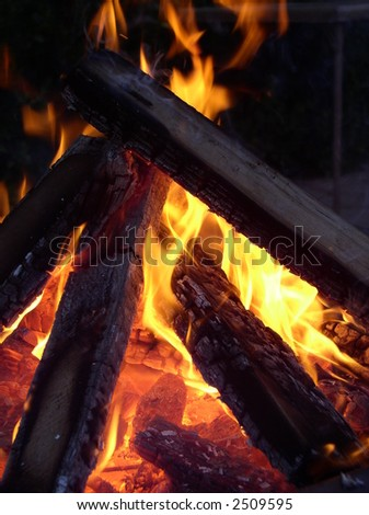 flames entwining around burning logs - stock photo
