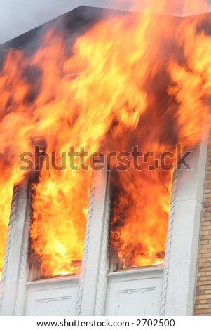 Flames shooting out of the windows of a burning apartment - stock photo
