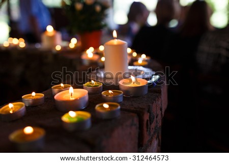 Flaming candles at the funeral ceremony indoor - stock photo