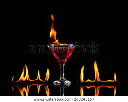 Flaming cocktail over black - stock photo