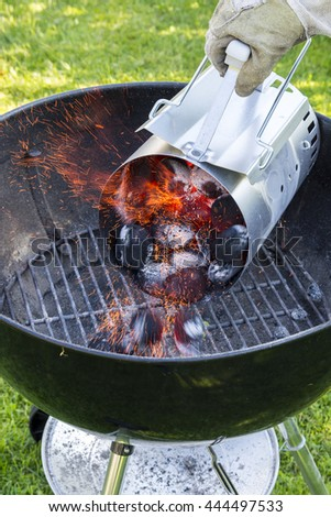 Flaming hot red yellow charcoal briquettes in a grill starter - stock photo
