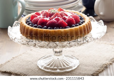 flan case with blueberries, strawberries, raspberries on a glass cake stand - stock photo