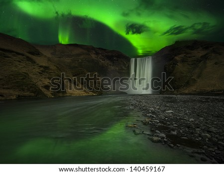 Flash of Aurora polaris above skogafoss waterfall, iceland - stock photo