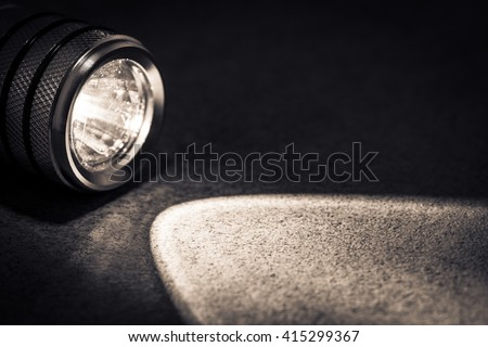 Flashlight and a beam of light in darkness. A modern led light with bright projection on dark stone. Surface with copy space. - stock photo