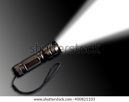 Flashlight or torch shining beam of light isolated on black to grey background. - stock photo