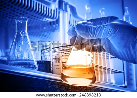 Flask in scientist hand with laboratory background  - stock photo