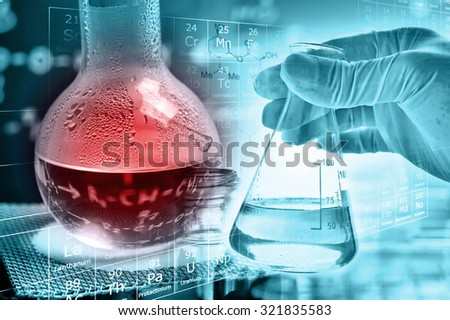 Flask in scientist hand with round bottom glassware  - stock photo