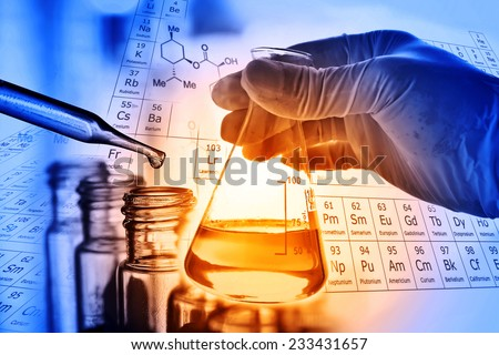 Flask in scientist hand with test tubes  - stock photo