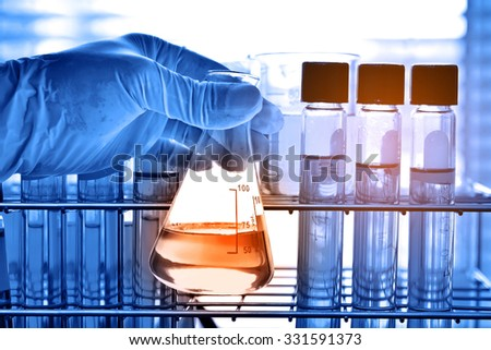 Flask in scientist hand with test tubes, laboratory research concept  - stock photo