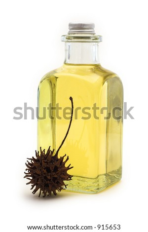 Flask of oil with sweetgum fruit on white background - stock photo