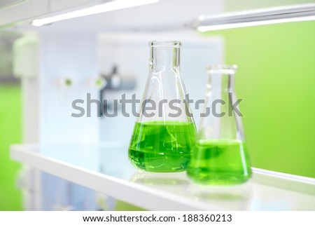 flasks with green liquid on the background of the chemical laboratory - stock photo