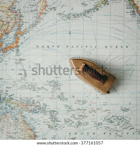 Flat lay adventure map with ship-like iron - stock photo