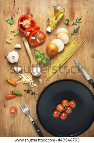Flat lay cutlery set and plate with freshly cut paste recipe ingredient on rustic wooden table top. - stock photo