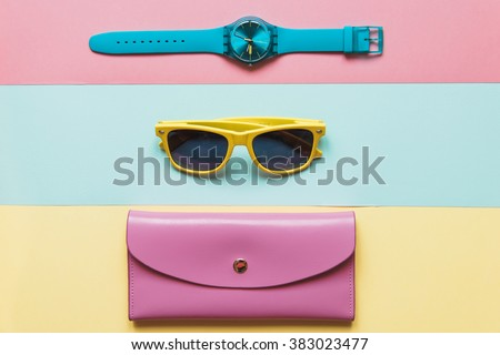 Flat lay fashion set: blue watch, pink purse and yellow sunglasses on yellow, pink and mint background in pastel colors - stock photo