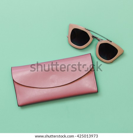 Flat lay fashion set: light pink sunglasses and light pink purse on pastel green and mint background. Top view. - stock photo