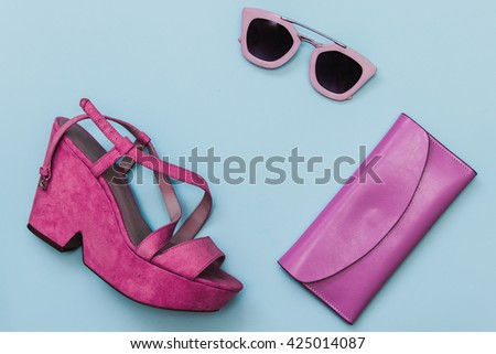 Flat lay fashion set: pink shoes with sunglasses and purse on pastel blue background. Top view. - stock photo