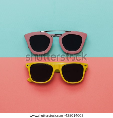 Flat lay fashion set:  two sunglasses on pastel backgrounds. Top view. - stock photo