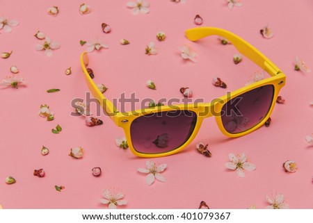 Flat lay fashion set with accessories: yellow sunglasses on pink background with flowers. Top view. - stock photo