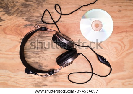 Flat lay - headphones and compact disc on wooden desk - stock photo
