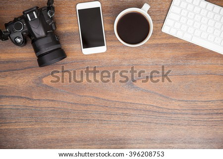 Flat lay of a photographers desk with a digital camera, a smartphone and some coffee with plenty of copy space - stock photo