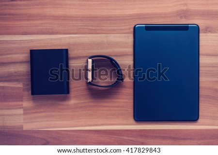Flat lay of clever new technology of today - portable charger powerbank, unknown smart wrist watch, tablet pc. Travel and connect to work and have fun from anywhere you want. Blue hipster toning - stock photo